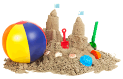 Sand castle with various summer toys in and around it.