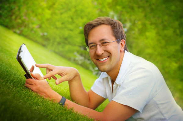 Accounts | Man laying on lawn at home smiling, using tablet
